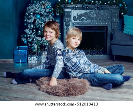 two brothers at hoe with Christmas tree and presents