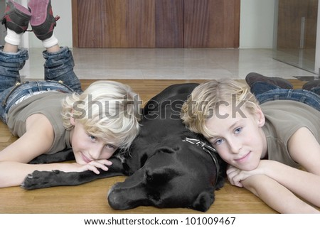 Two brothers at home relaxing on the floor their pet dog.