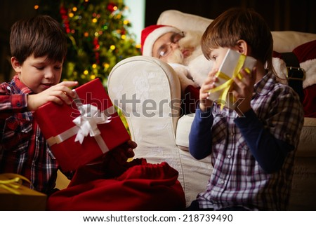 Two brothers choosing gifts from sack with Santa Claus sleeping on background - stock photo