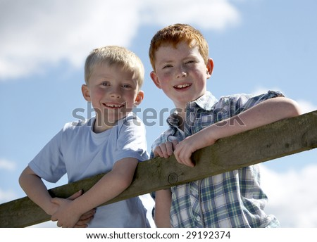 Two brothers climbing on a fence - stock photo