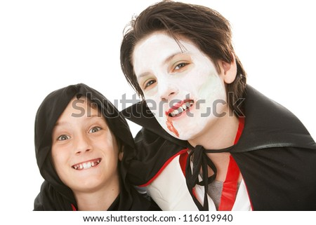 Two brothers dressed in their Halloween costumes.  One is a goblin and the other is a vampire.  White background. - stock photo