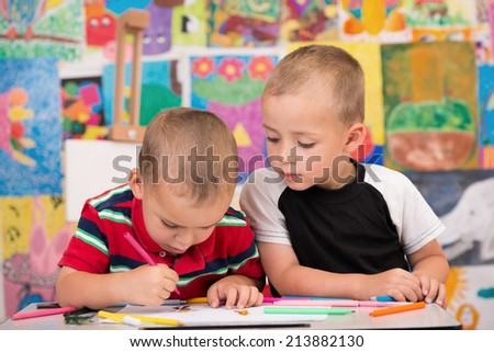 Two brothers enjoy drawing with felt tip pens. Selective focus on one child. - stock photo