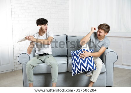 Two brothers fighting with pillows on sofa at home - stock photo