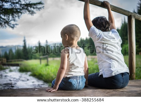Two brothers friends sitting and enjoying on the wooden bridge by mountain creek in beautiful nature - stock photo