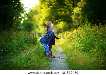 Two brothers having fun in the green wet forest after the rain on a sunny summer day - stock photo