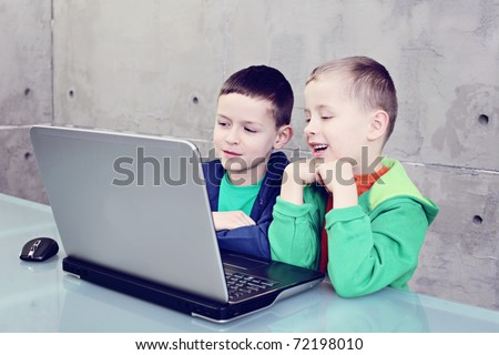 two brothers having fun with laptop - kids and family - stock photo
