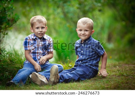 Two brothers hugging each other outdoor, smiling and laughing