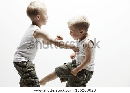 Two brothers in a battle. Big brother punching the younger brother in his stomach - stock photo