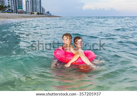 two brothers in a swim ring have fun in the ocean