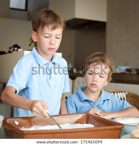Two brothers make a cake in kitchen