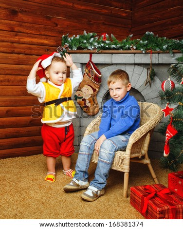 Two brothers near decorated Christmas tree pending holiday
