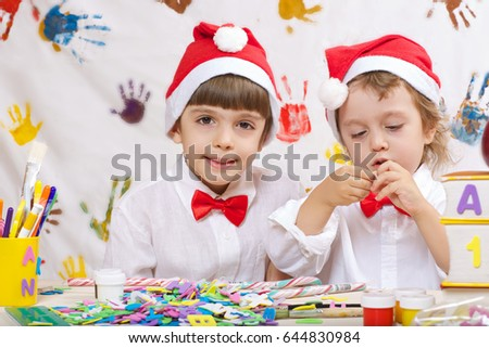 Two brothers of 7 and 4 years old dressed in white shirts and Santa's hats are playing together.