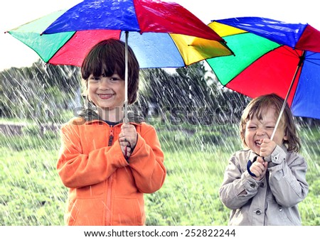 two brothers play in rain outdoors - stock photo