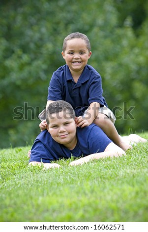 Two brothers playing on fresh green grass - stock photo