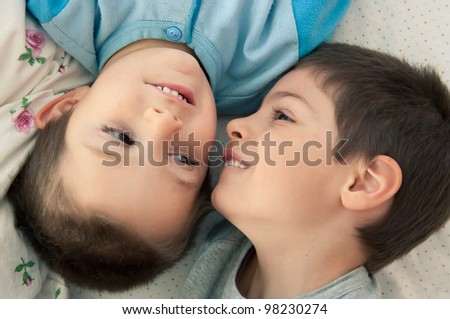 Two brothers portrait laying on bed. - stock photo