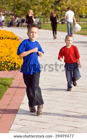 Two brothers run on pathes of city park - stock photo