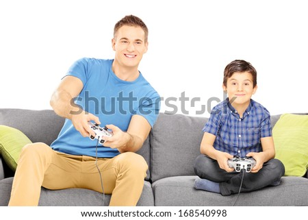Two brothers seated on a sofa playing video game isolated against white background - stock photo