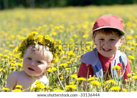 Two brothers seating in spring flowers in field of dandelions