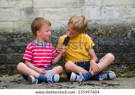 Two brothers sharing an ice lolly - stock photo
