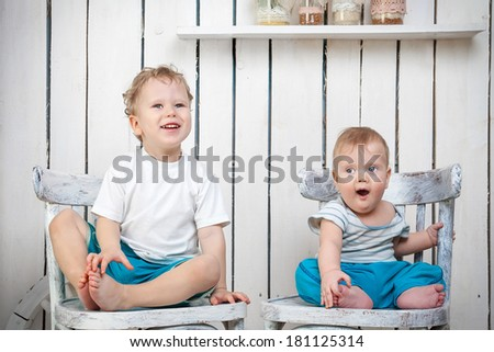 Two brothers sitting on chairs in country house - stock photo