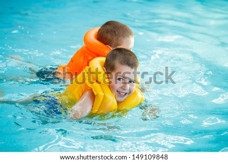 Two brothers swimming in life jacket  - stock photo