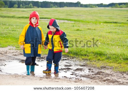 Two brothers walking in a mud puddle - stock photo