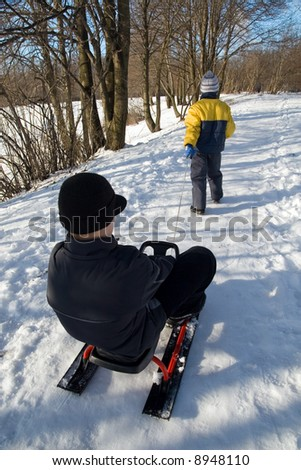 Two brothers with toboggan in the winter park - stock photo