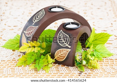 Two brown candle nests with green leaves on white tablecloth. - stock photo