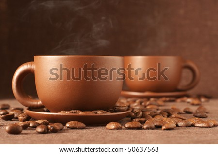 Two brown ceramic cups of coffee with steam and coffee beans on brown canvas.