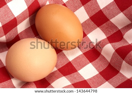 Two brown eggs on a tablecloth.