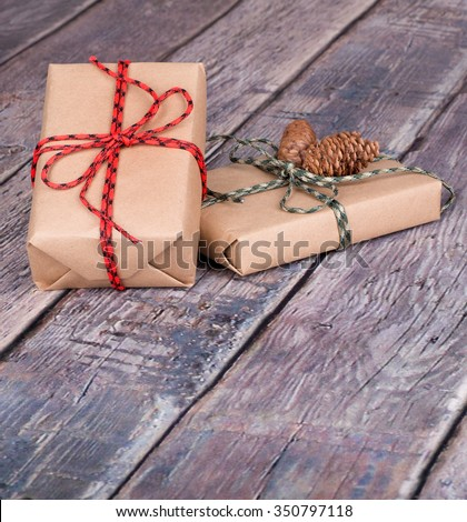 Two brown gift boxes tied with string on a wood textured surface