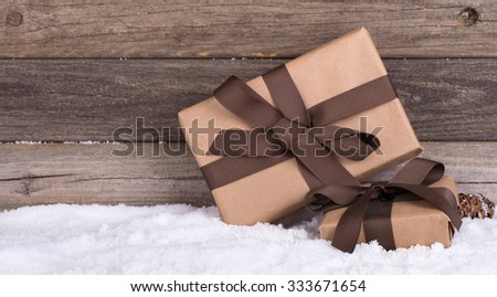 Two brown gift packages on snow with a wood background