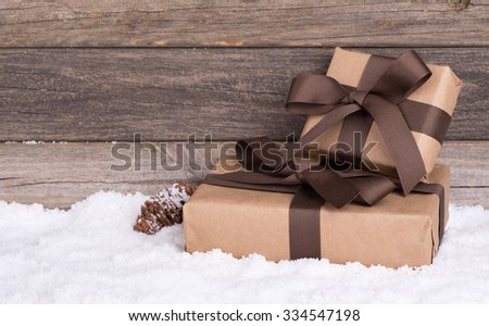 Two brown gift packages on snow with a wood background - stock photo