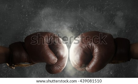 Two brown old boxing gloves hit together - stock photo