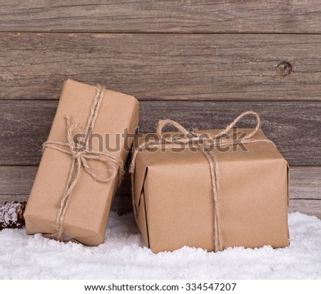 Two brown packages on snow with wood background