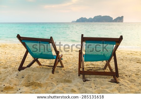 Two brown sunbeds on sunset on yellow sand tropical beach Thailand - stock photo