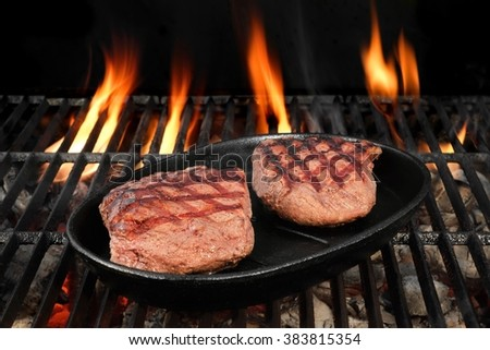 Two Browned Strip Beef Steaks In The Cast Iron Frying Pan On The Hot BBQ Charcoal Grill With Bright Flames On The Black Isolated Background, Top View, Close-Up - stock photo