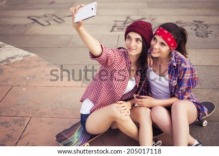 Two Brunette teenage girls friends in hipster outfit (jeans shorts, gumshoes, plaid shirt, hat) with a skateboard at the park outdoors make selfie on a phone. Copy space - stock photo