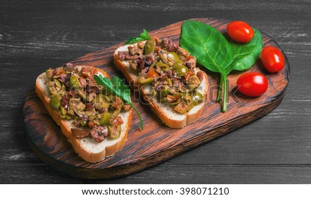 Two bruschetta sandwich with capers, kalamata olives and fresh herbs, cherry tomatoes red, spinach leaves, parsley, served on the Board at a gray wooden surface - stock photo