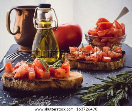 Two bruschettas with fresh tomato and rosemary - stock photo
