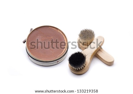 two brushes and a pot of grease to clean leather shoes