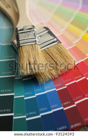 Two brushes with wood handle on a color palette - stock photo