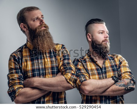 Two brutal bearded hipsters dressed in a plaid shirt posing on grey background in a studio.