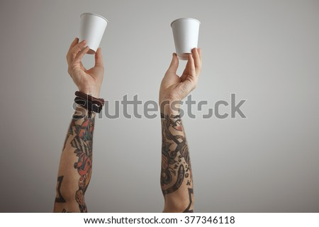 Two brutal tattooed men hands hold blank paper take away cardboard glass in the air. presentation isolated on white. - stock photo