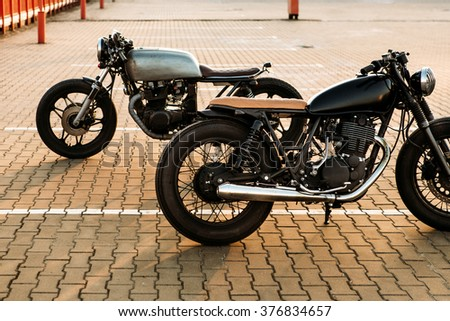 Two brutal vintage custom motorcycle cafe racer looking in opposite directions on empty rooftop parking lot with during sunset. Symbol of wild ride, straight road, urban style, hipster lifestyle.