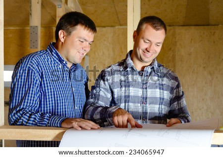 Two builders discussing a building plan as they stand in the interior of a new build timber frame house still under construction