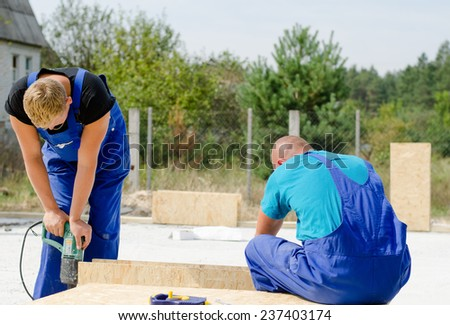 Two builders in dungarees installing insulated wall panels on a residential building site using an electric drill to drill holes in the wood - stock photo