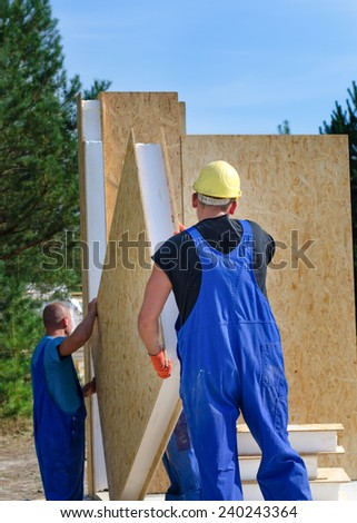 Two builders installing an insulated wooden wall panel on a construction site for a new build house working outdoors in the sunshine - stock photo