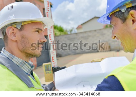 Two builders looking at plans - stock photo