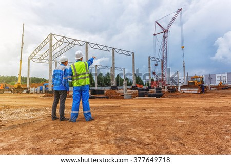 Two builders turning back point to the crane